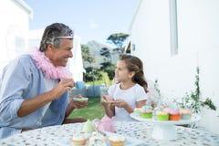 父亲和女儿有神仙的服装的茶会 免版税库存照片