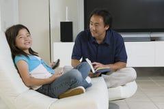父亲和女儿有遥控和书的在家 图库摄影