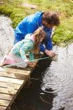 父亲和女儿渔在有网的池塘 免版税库存照片