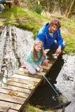 父亲和女儿渔在有网的池塘 免版税图库摄影