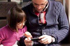 父亲和女儿火车的有巧妙的电话的 图库摄影