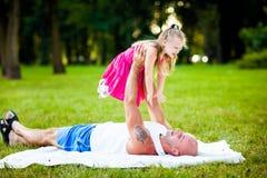 父亲和女儿获得乐趣在公园 免版税图库摄影