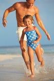 父亲和女儿获得乐趣在海滩假日的海 库存图片