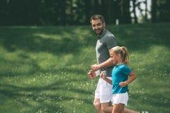 父亲和女儿跑步 免版税库存照片