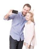 父亲和女儿采取与电话的一照片selfie 免版税库存照片