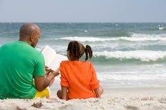 父亲和女儿读书 库存照片
