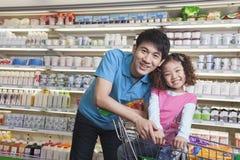 父亲和女儿购物在超级市场,看照相机 免版税库存照片
