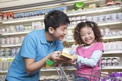父亲和女儿购物在超级市场 免版税库存图片