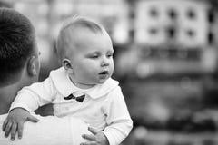 父亲和子项 父亲胳膊的逗人喜爱的男婴 免版税库存图片