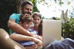 父亲和孩子使用膝上型计算机在庭院里 免版税库存照片