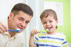 父亲和孩子儿子掠过的牙在卫生间里 免版税图库摄影