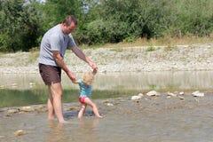 父亲和孩子在河 免版税图库摄影