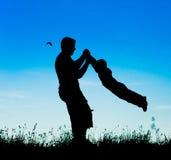 父亲和孩子的一个愉快的家庭的剪影 免版税库存图片