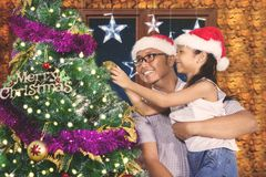 父亲和孩子装饰一棵杉树 免版税库存图片
