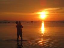 父亲和孩子,在海滩泰国的日落 库存照片