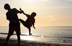 父亲和小儿子现出轮廓戏剧在日落 免版税图库摄影