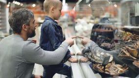 父亲和小儿子看食物通过玻璃在超级市场,人指向产品,笑和 股票录像