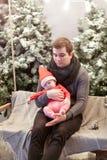 父亲和小儿子红色圣诞老人帽子的坐木摇摆在积雪的圣诞树旁边 查找下来 图库摄影