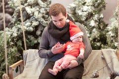 父亲和小儿子红色圣诞老人帽子的坐木摇摆在积雪的圣诞树旁边 免版税库存照片