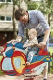 父亲和小儿子获得乐趣在操场 免版税图库摄影