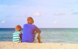 父亲和小儿子谈话在海滩 免版税库存图片