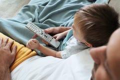 父亲和小孩一起看电视并且交换与遥控的新的节目 免版税库存图片