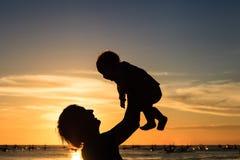 父亲和小的女儿剪影在日落靠岸 免版税库存照片