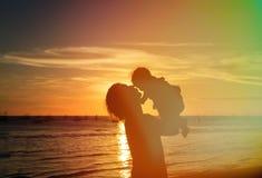 父亲和小的女儿剪影在日落 免版税库存照片