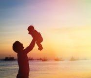 父亲和小的女儿剪影在日落 库存照片