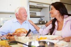 父亲和成人女儿有家庭膳食在表上 免版税库存图片
