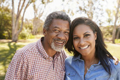 父亲和成人女儿画象在一起公园 免版税库存图片