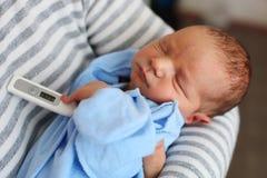父亲和新出生的儿子有温度计的 免版税库存图片