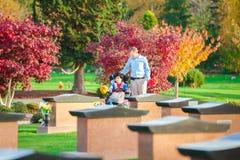父亲和残疾儿子轮椅参观的gravesite的在cem 免版税库存照片
