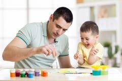 父亲和获得三的年的小男孩在家绘的乐趣 免版税库存图片