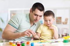 父亲和获得三的年的小男孩在家绘的乐趣 库存图片