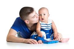年轻父亲和获得的女婴与音乐玩具的乐趣 库存照片