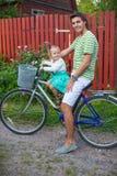 年轻父亲和逗人喜爱的小的女儿骑马骑自行车 图库摄影