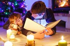 父亲和逗人喜爱的小的小孩男孩阅读书由烟囱、蜡烛和壁炉 免版税库存图片