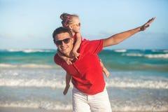 年轻父亲和他可爱的矮小的女儿 免版税库存图片