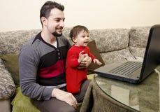 父亲和婴孩个人计算机的 免版税库存图片