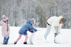 年轻父亲和他的两个女儿在冬天停放 免版税库存照片
