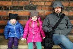年轻父亲和他的两个小女儿坐长凳 库存图片