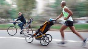 父亲和他们的孩子沿街道移动 免版税库存图片