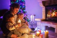 年轻父亲和他的小儿子由壁炉坐克里斯 免版税库存照片