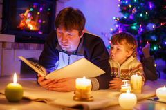 年轻父亲和他的小孩阅读书由壁炉 库存图片