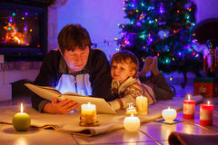 年轻父亲和他的小男孩阅读书由一个壁炉在C 免版税库存图片