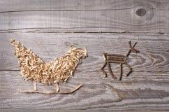父亲圣诞节雪橇的简单的标志从由干燥木棍子和驯鹿安排了做的锯木屑在木灰色背景 库存照片