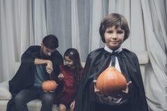 父亲在万圣夜帮助孩子雕刻南瓜,在他们前面的男孩立场用另一个南瓜 库存照片