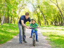 父亲在公园教他的儿子骑一辆自行车 图库摄影