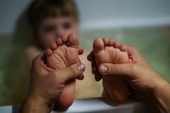 父亲在卫生间里拿着充满爱的婴孩脚跟 库存照片